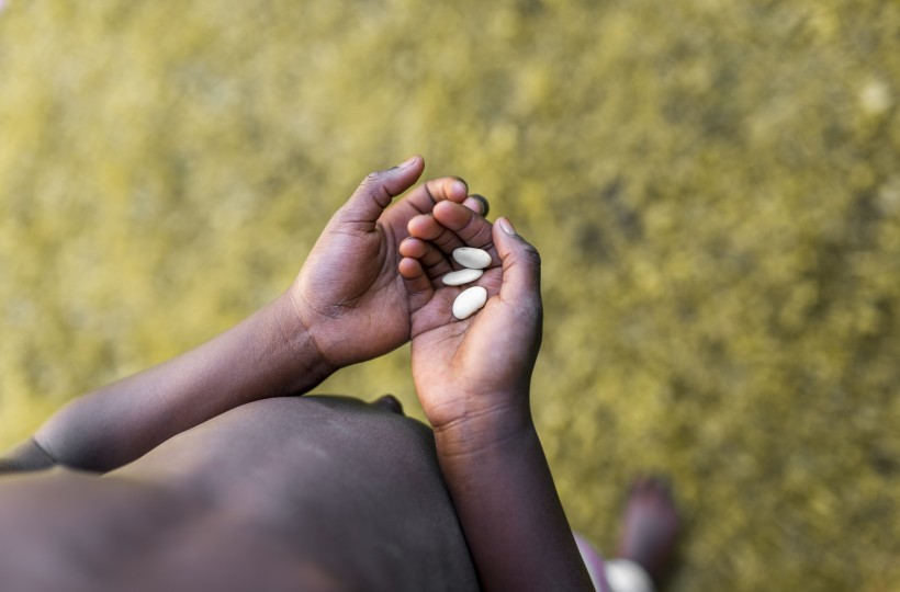 Top view of poor african child hands holding three white beans. Concept of Hunger in Africa.